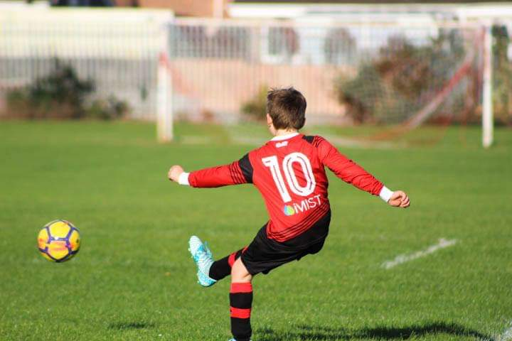 little boy kicking a football with a iMist sponsored shirt on